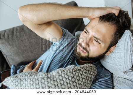 Feeling sick. Sad nice handsome man holding his forehead and hugging a cushion while feeling bad