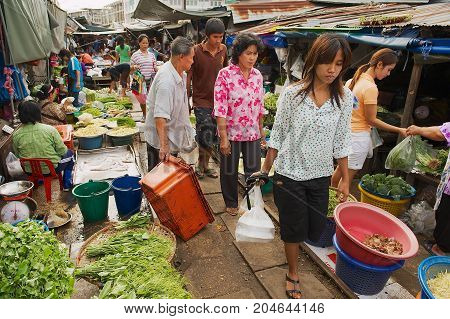 SAMUT SONGKRAM, THAILAND - MAY 23, 2009: Local people do shopping at the Mae Klong railway tracks market in Samut Songkram, Thailand. This market is famous for its location on active railroad line.