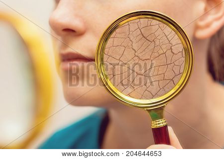 aging and dry face skin concept - woman with magnifying glass