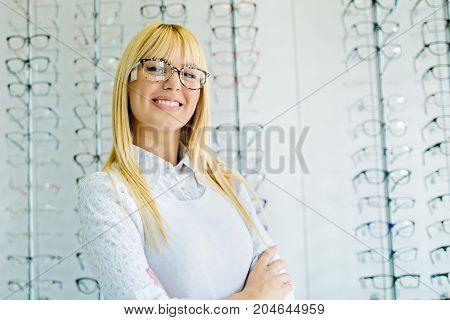 Beautiful blonde woman choosing glasses in optics store.