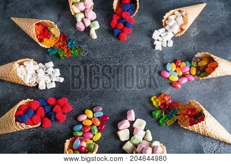 Round frame made of colorful bright assorted candy in waffle cones. Sweety food. Flat lay, top view