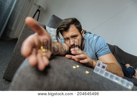 Very weak. Unhappy cheerless moody man lying on the sofa and trying to reach his medicine while feeling very weak