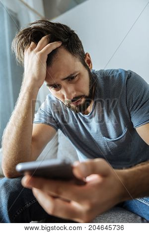 This is a dead end. Depressed sad bearded man holding his forehead and looking at the smartphone screen while feeling unhappy