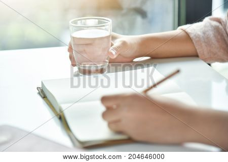 Happy Asian woman holding glass of water while writing on notebook or diary with white desk in bedroom. Copy space.