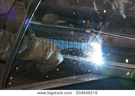 Metalworking shop workers work behind machines and apparatuses to create steel structures.