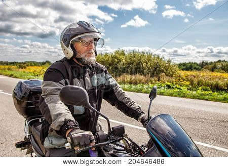 elderly motorcyclist wearing a jacket and glasses with a helmet sitting on his motorcycle on the road