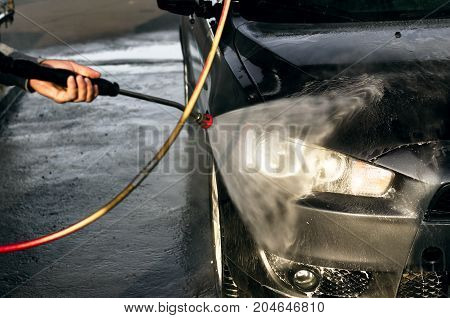 Car washing. Car cleaning using high pressure water. Worker washes the car.