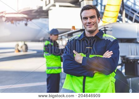 Portrait of cheerful male worker situating on airdrome. He looking at camera while colleague checking machine