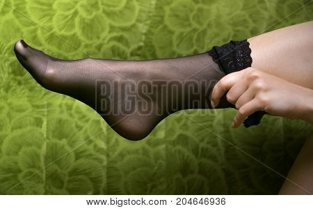 Sexy female feet in black stockings on green sofa. Woman clothe stockings on her legs.