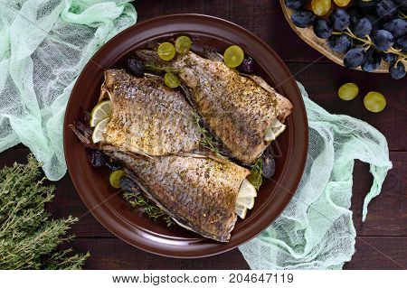 Baked carp with grapes and herbs on a ceramic dish on a dark wooden background. Top view.