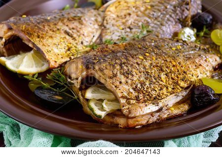 Baked carp with grapes and herbs on a ceramic dish on a dark wooden background.