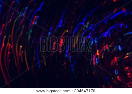 Abstract picture of colorful lines in motion on black background. Bokeh of defocused curves spinning into spiral, blurred neon blue and red leds, galaxy, magic space and stars wallpaper