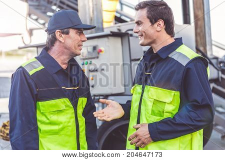 Cheerful male worker speaking with happy colleague while situating in airdrome