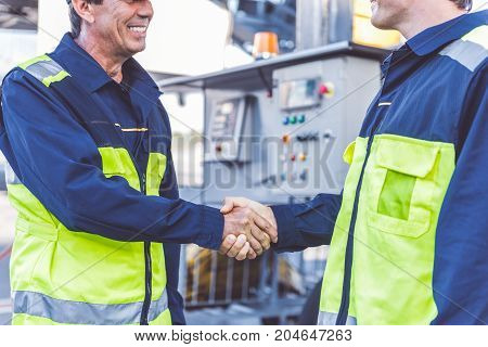 Outgoing young technical staff shaking comrade hand while having job on airport