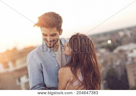 Couple in love standing at a building rooftop enjoying a beautiful sunset over city skylines and hugging
