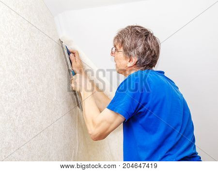 elderly worker in protective gloves with spatula smoothing wallpaper in his house