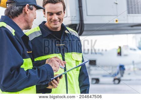 Portrait of cheerful technical staff looking at document while speaking with comrade at airport outdoor. Copy space