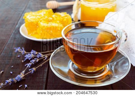 A cup of tea and honeycomb on a dark wooden table.