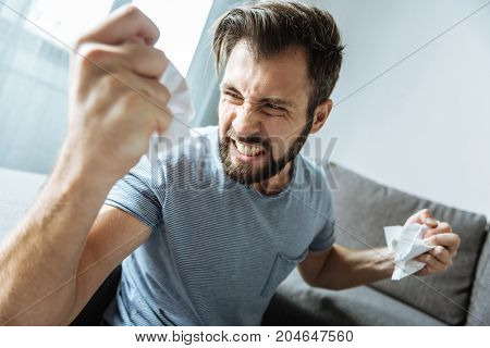 Emotion of anger. Unhappy brutal bearded man clenching his teeth and looking at his hand while crumpling paper