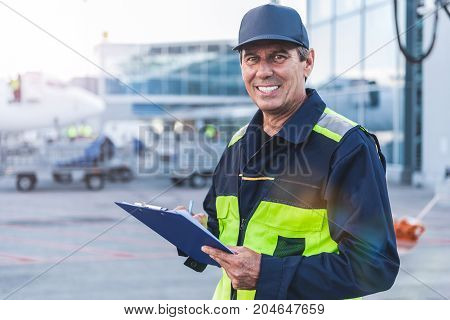 Portrait of beaming technical staff making notes at airdrome. He looking at camera. Copy space