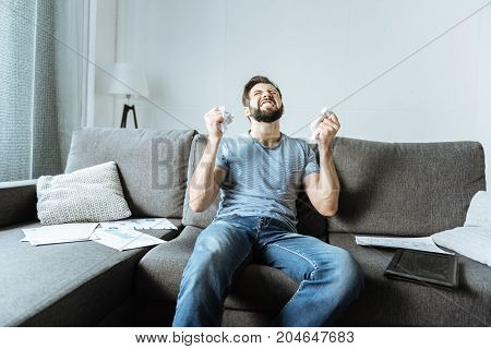 Why is it happening. Depressed unhappy bearded man sitting on the sofa and crumpling paper while expressing his anger