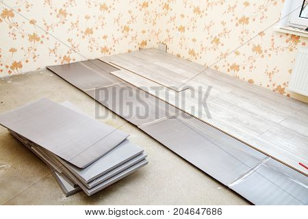laminate boards prepared for laying on the floor in the room closeup