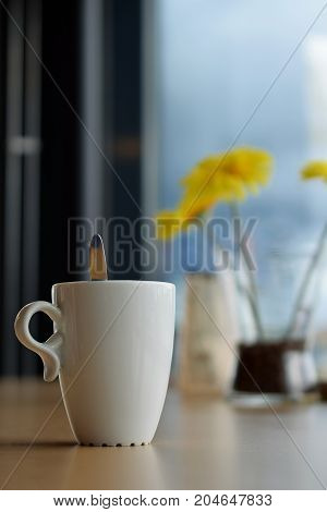 Mug of coffee on table in cafe. Focus on cup on foreground, yellow flowers on background. Vertical image.