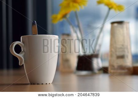 Cup of coffee on table in cafe. Focus on mug on foreground, yellow flowers on background.