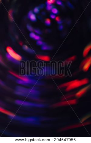 Abstract background of colorful blurs in motion on black. Bokeh of defocused streaks spinning into spiral, blurred neon blue and red leds, glowing city lights, banners of space and ufo