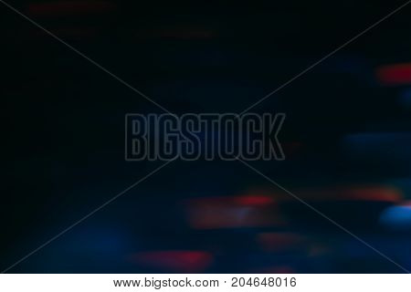 Abstract background of colorful blurs in motion on black. Bokeh of defocused streaks, blurred neon blue and red leds, wallpaper of glowing city lights and traffic