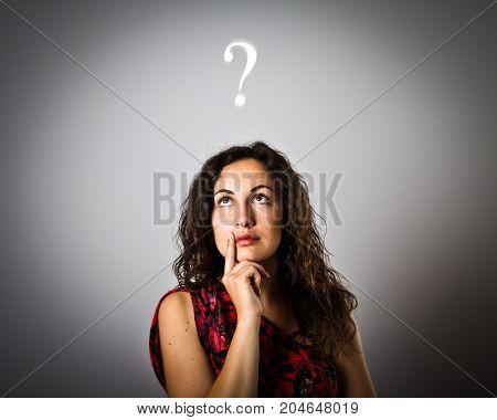 Girl is full of doubts and hesitation. Girl and question mark above head. Young woman is doing something.