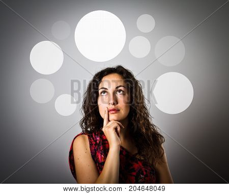 Girl is having an idea with gray bubbles over her head. Girl is full of doubts and hesitation. Young woman is doing something.