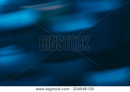 Abstract background of colorful blurs in motion on black. Bokeh of defocused streaks, blurred neon blue leds, glowing city lights and traffic, wallpapers and banners