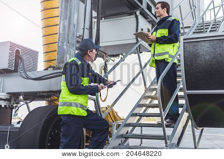 Full length side view beaming technical staff looking away while standing on stairs near machine. Serene colleague watching at him