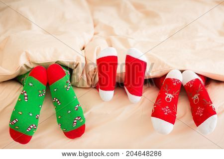 Family in Christmas socks lying on bed. Mother father and baby having fun together. People relaxing at home. Winter holiday Xmas and New Year concept