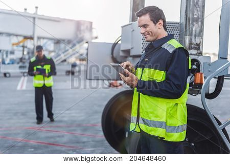 Side view smiling technical staff watching at electronic tablet while standing near machine at airdrome. Comrade going to him