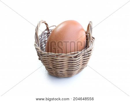 Close up of chicken egg in a basket isolated on white background