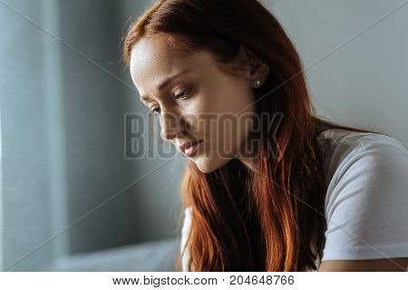 State of melancholy. Cheerless beautiful red haired woman being at home and feeling melancholic while having difficult times in life