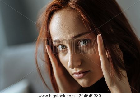 Troubled look. Portrait of an upset cheerless young woman holding her temples and looking at you while feeling pain