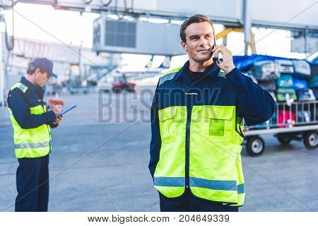 Portrait of cheerful young male worker telling by mobile at airdrome. Side view colleague writing document