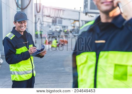 Portrait of beaming technical staff noting remark while keeping clipboard at airport. He looking at camera. Partner speaking by phone