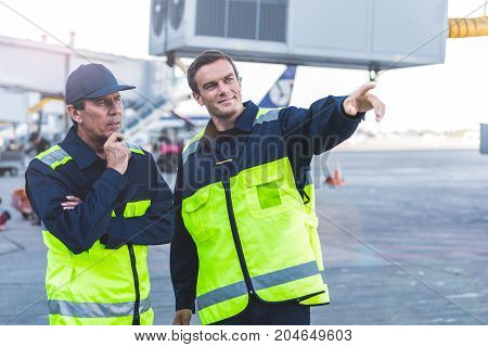 Portrait of smiling engineer flourishing arm. Doubting comrade looking at distance at airdrome