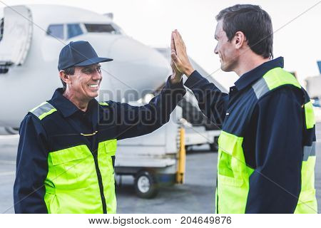 We are good team. Outgoing technical staff slapping hands of each other at airdrome