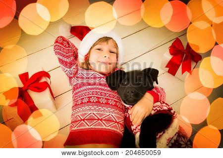 Happy child and dog with Christmas gift. Kid dressed in Santa Claus hat. Baby having fun at home. Xmas holiday concept