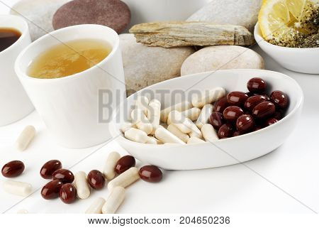 Diet pills with arrangement of coffee and tea cups