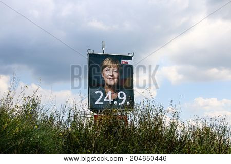 MAGDEBURG, GERMANY - September 17, 2017: One of the largest election poster in Germany of Federal Chancellor Angela Merkel (CDU) next to the Autobahn No. 2 near Magdeburg. German election 2017.