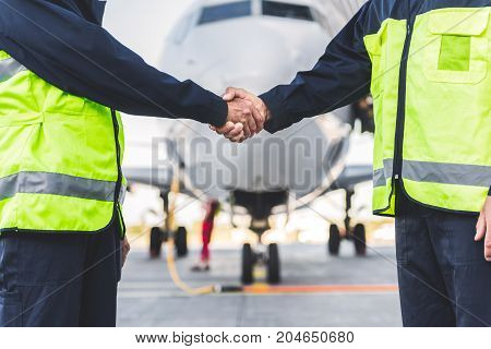 We are good team. Close up male technical staff hand shaking each other arms while having job at airdrome. Friendship concept