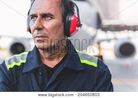 Portrait of serious technical staff looking away while locating at airdrome. He wearing protective earmuffs