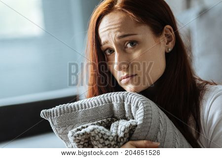 I am all alone. Sad red haired gloomy woman holding a cushion and thinking about her loneliness while being at home