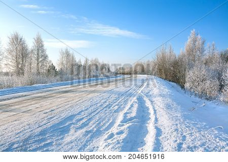beautiful winter landscape with asphalt roadforest and blue sky. frozen wintry day and path drive